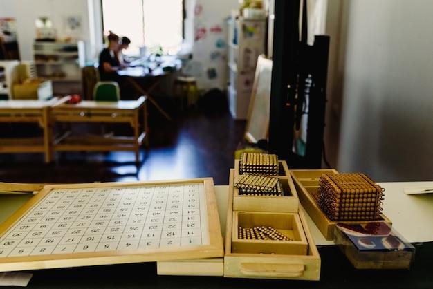 Tisch und regale mit montessori-material, farbigen gegenständen und holzzylindern