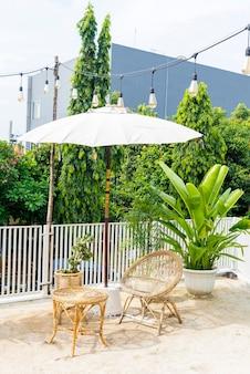 Tisch und stuhl auf der terrasse mit grünen pflanzen