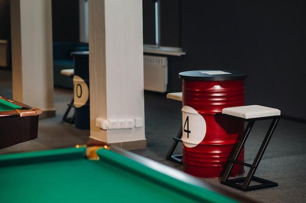 Tisch und zwei stühle neben dem grün gedeckten billardtisch mit bällen im billardclub.