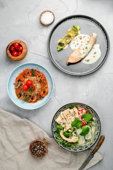 Tisch voller meeresfrüchte. lachssteak gegrillte garnelen und tintenfischsalat mit avocado-draufsicht, meeresfrüchte-tischkonzept