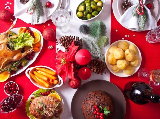 Tisch zum erntedankfest oder weihnachtsessen. gefüllter gebratener truthahn im vordergrund. traditioneller feiertag. draufsicht.
