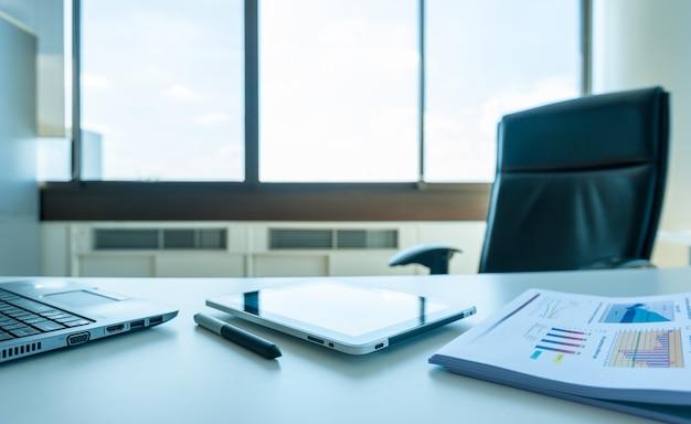 Tischarbeit im leeren büroraum des managers mit tablet und bericht mit laptop