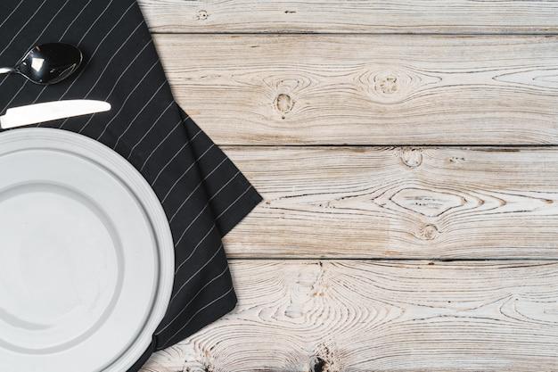 Tischaufbau mit tellern auf dunklem holz