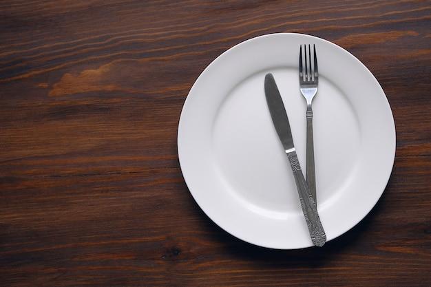 Tischbesteck auf einer leeren weißen platte, auf einem hölzernen hintergrund. gabel und löffel in eine schüssel geben. das konzept des essens. kopieren sie den platz für den text.