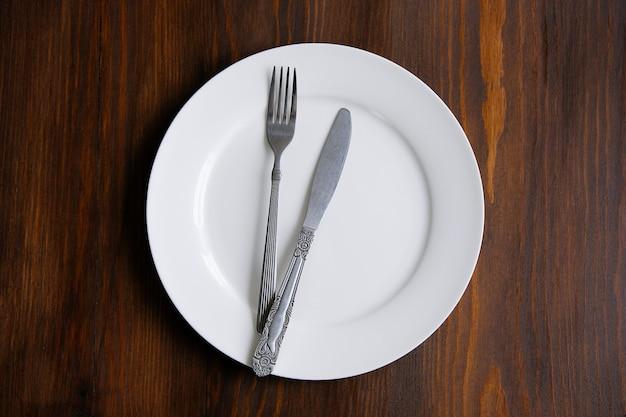 Tischbesteck auf einer leeren weißen platte, auf einem holztisch. das konzept des essens.
