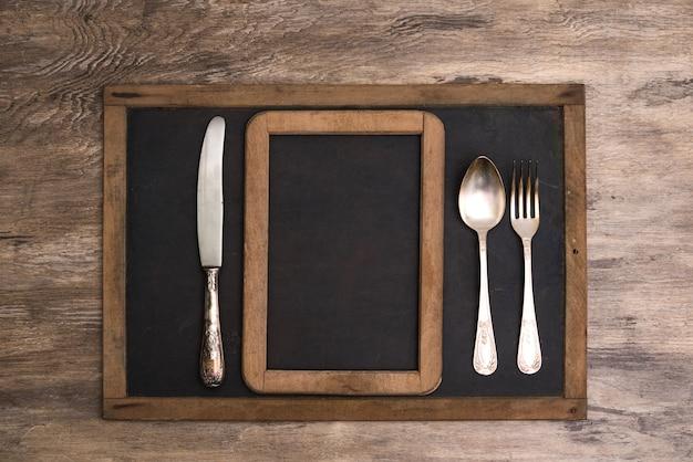 Tischbesteck auf weinlesetafel für menü