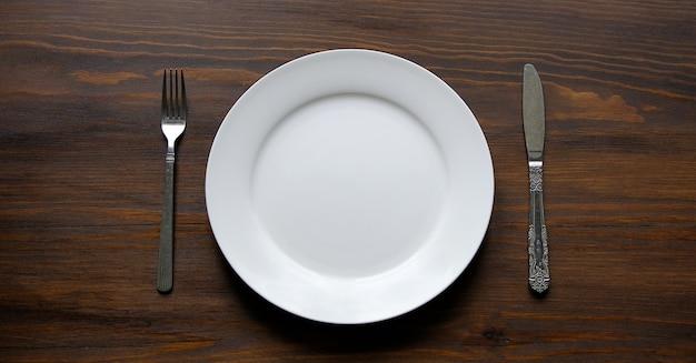 Tischbesteck und eine leere saubere weiße platte, auf einem hölzernen hintergrund. gabel und löffel in der nähe der schüssel. essen. kopieren sie den platz für den text. banner.
