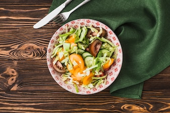 Tischbesteck und Serviette nahe Schüssel mit Salat