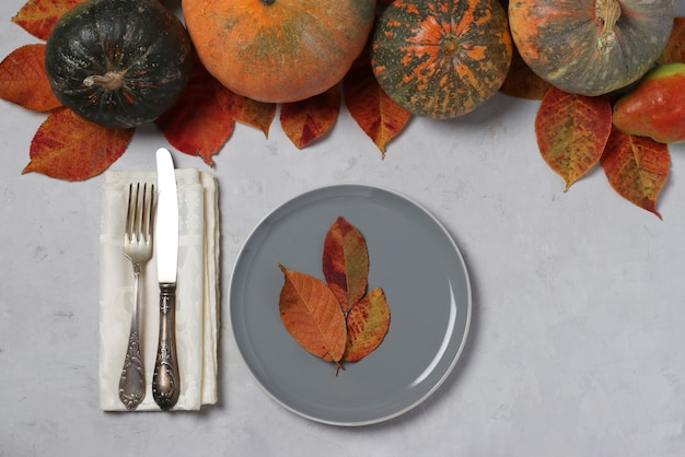 Tischdekoration am erntedankfest dekorierte kürbis, birnen und bunte blätter auf grau. sicht von oben