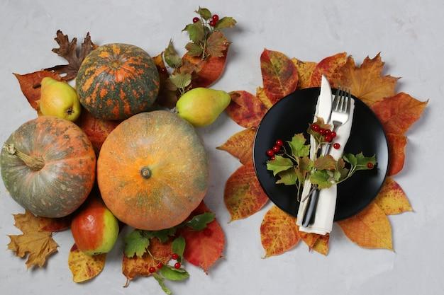 Tischdekoration am erntedankfest dekorierte kürbis, viburnum, birnen und bunte blätter auf grauer oberfläche. draufsicht
