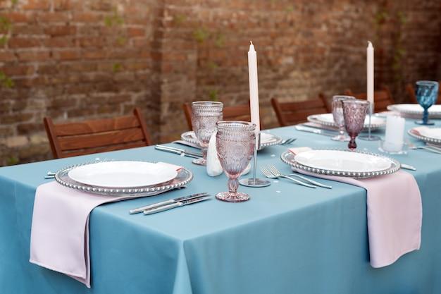Tischdekoration für feiertage und hochzeitsessen. tabelle stellte für feiertagshochzeitsempfang restaurant im im freien ein.