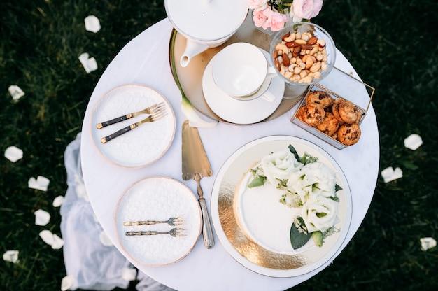 Tischdekoration, keramik-teekanne, teetassen, kuchen und blumen, nahaufnahme, seitenansicht, niemand. luxusbesteck auf weißer tischdecke, geschirr im freien