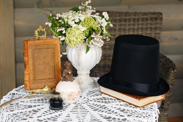Tischdekoration mit blumen und einem buch, tischdekoration für ein abendessen bei kerzenschein.