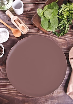 Tischdekoration mit braunem teller mit küchengerät auf dem holztisch. draufsicht. Premium Fotos
