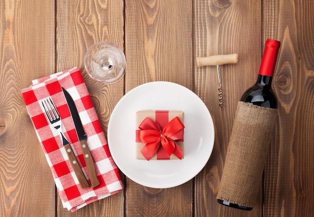 Tischdekoration mit geschenkbox auf teller, weinglas und rotweinflasche. blick von oben über rustikalen holztischhintergrund