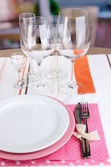 Tischdekoration mit gläsern für verschiedene getränke auf dem tisch auf raumhintergrund