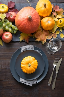 Tischdekoration mit orangefarbenen blättern und kürbissen. erntedank.