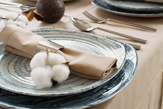 Tischdekoration mit stilvollem geschirr auf beiger tischdecke