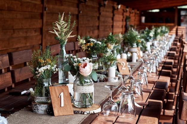 Tischdekoration mit weißen blumen und kerzen für ein hochzeitsfest.