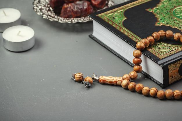 Tischdekoration ramadan kareem dattelfeiertag mit rosenkranz und dem heiligen buch des korans