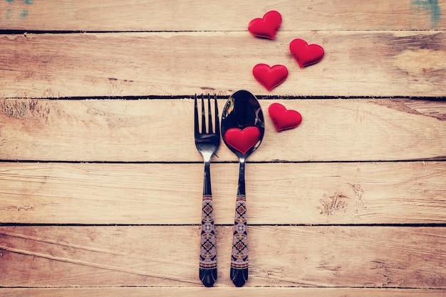 Tischdekoration und rotes herz zum abendessen valentinstag.