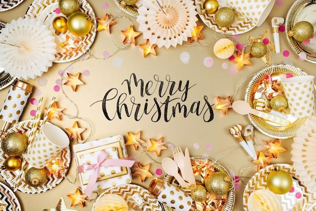 Tischdekoration zu weihnachten. rahmen aus goldenem partydekorationszeug. flache lage, ansicht von oben