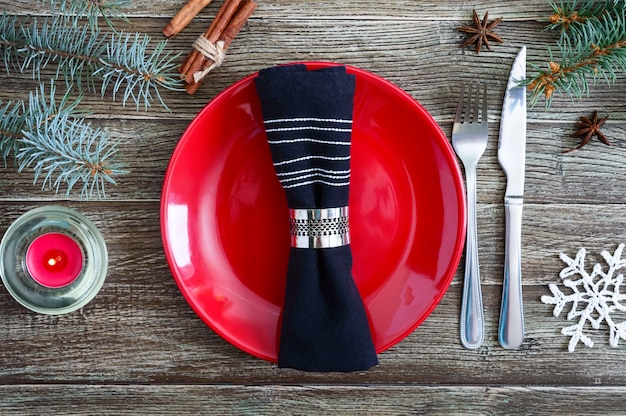 Tischdekoration zu weihnachten. rote platte, gabel, messer, zweig eines weihnachtsbaumes auf einem hölzernen hintergrund. weihnachten weihnachten neujahr urlaub hintergrund.