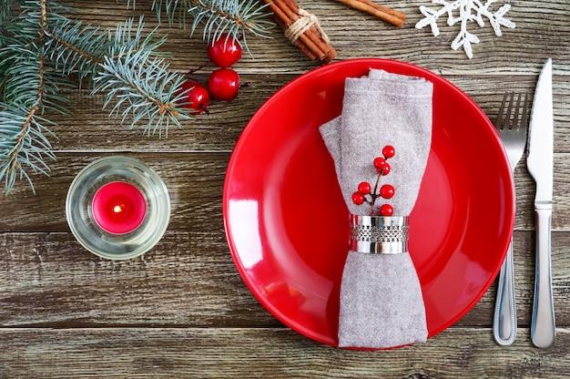 Tischdekoration zu weihnachten. roter teller, serviette, gabel, messer, ast eines baumes auf einem holztisch. weihnachten, neujahr urlaub hintergrund. die draufsicht