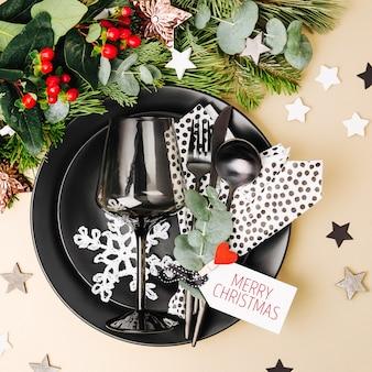 Tischdekoration zu weihnachten. schwarzes geschirr und dekoration mit tannenzweig. flache lage, ansicht von oben.