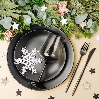 Tischdekoration zu weihnachten. schwarzes geschirr und dekoration mit tannenzweig.