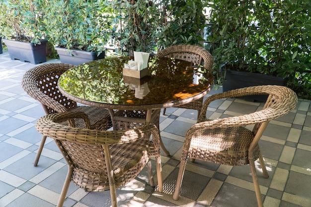 Tische und korbstühle im sommercafé im freien mit blumenbeeten