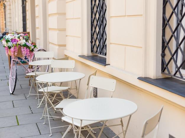 Tische und stühle des cafés im freien. straßencafé-tische im freien bereit für den service.