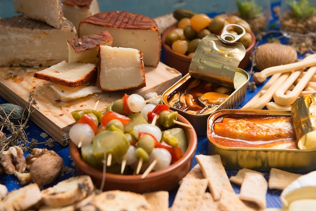 Tischgarnitur mit aperitif bestehend aus verschiedenen speisen käse und dosen essiggurken