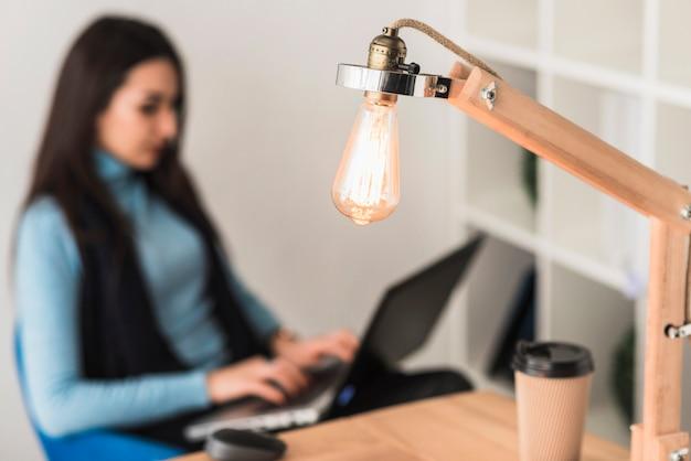 Tischlampe in der nähe von berufstätiger frau
