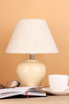 Tischlampe mit tasse und gläsern auf beige