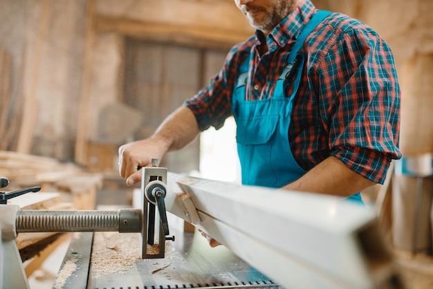 Tischler arbeitet an hobelmaschinen, holzbearbeitung, holzindustrie, zimmerei. holzverarbeitung auf möbelfabrik
