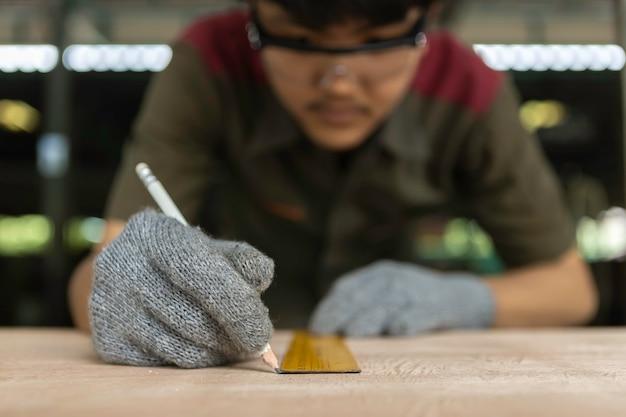 Tischler, der an holzbearbeitungsmaschinen in der zimmerei arbeitet. erfahrener tischler, der ein stück holz in seiner holzarbeitwerkstatt schneidet.