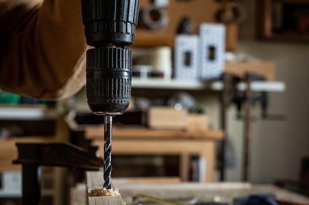 Tischler, der ein bohrgerät mit einem kreisel auf einem hölzernen brett macht