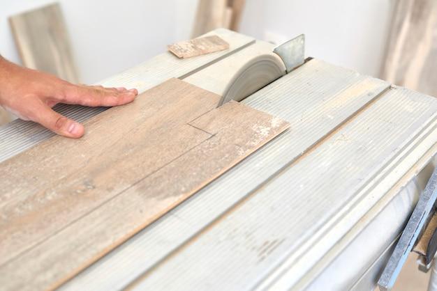 Tischler, der ein laminatholz vor der installation auf dem boden schneidet