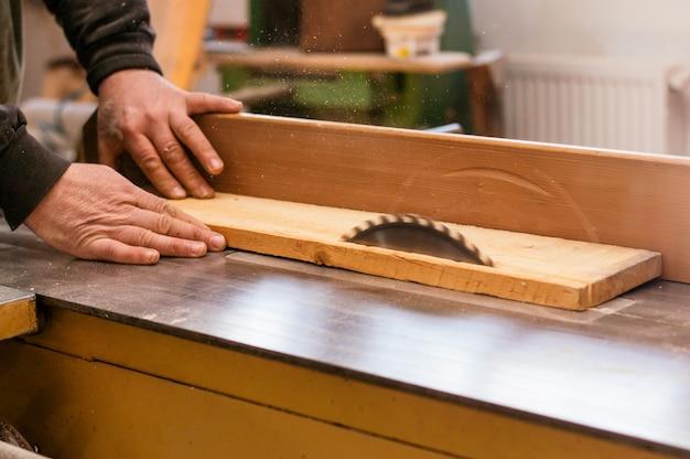 Tischler, der eine hölzerne planke schneidet