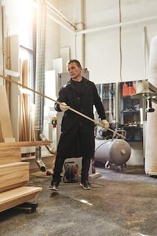 Tischler, der in der vertikalen aufnahme der holzfabrik arbeitet