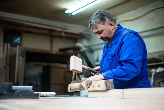 Tischler, der in der werkstatt, eine arbeitskraft plant einen baum mit einem hobel arbeitet