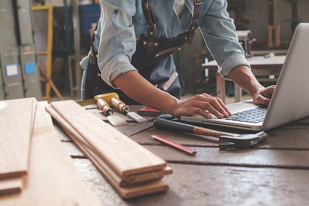 Tischler, der mit ausrüstung auf holztisch in der zimmerei arbeitet. frau arbeitet in einer tischlerei.