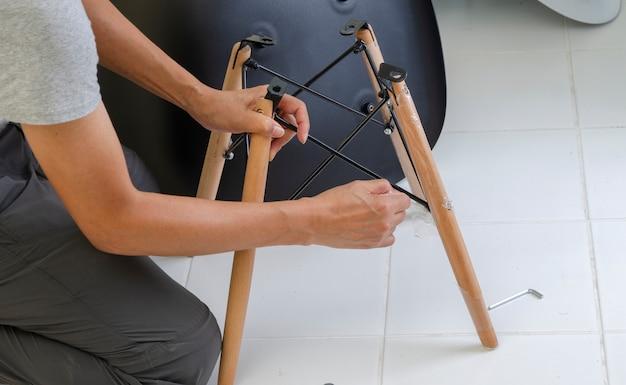Tischler, der teile des stuhls zusammenfügt