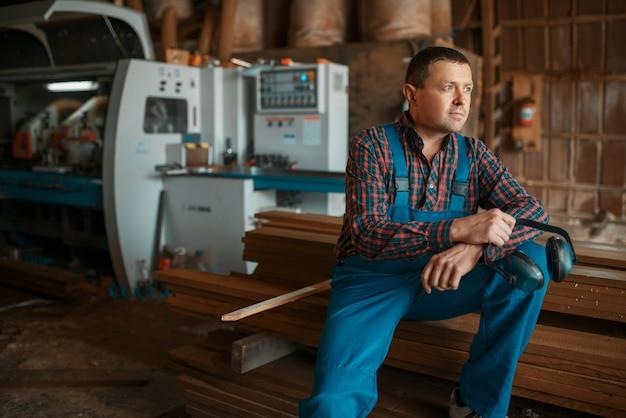 Tischler in uniform an seinem arbeitsplatz auf holzmühle, holzbearbeitungsmaschine, holzindustrie, zimmerei. holzfabrik, waldsägen im holzplatz