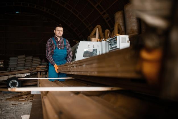 Tischler in uniform hält stapel von brettern, holzbearbeitungsmaschine, holzindustrie, zimmerei. holzverarbeitung auf fabrik, waldsägen im holzplatz, sägewerk