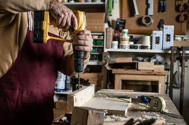 Tischler mit einem gelben bohrgerät, das an bord ein loch mit einem hölzernen bohrgerät macht