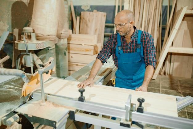 Tischler schneidet holzbrett auf kreissägemaschine, holzbearbeitung, holzindustrie, zimmerei.