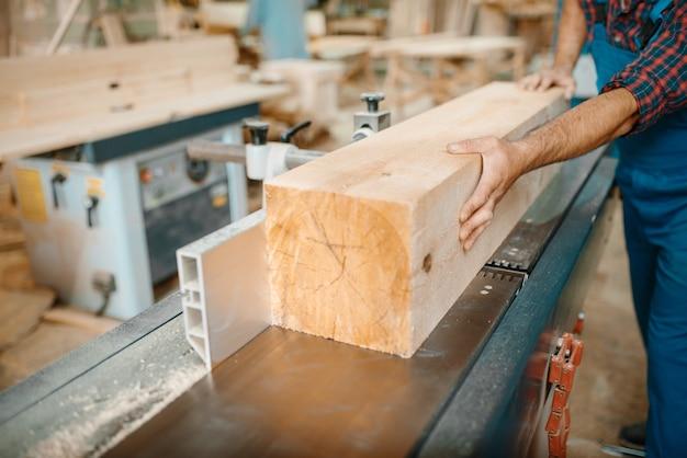 Tischler verarbeitet holzbalken auf hobelmaschine, holzbearbeitung, holzindustrie, zimmerei. holzverarbeitung auf möbelfabrik
