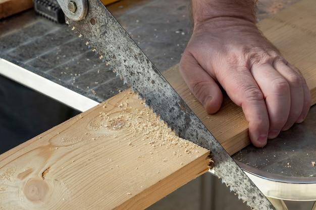 Tischlerhand mit dem alten handsaw, der hölzerne bretter schneidet. zimmerei, bau.